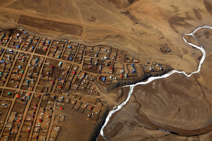 A frozen river is seen next to a group of houses located on the outskirts of the Mongolian capital city of Ulaanbaatar April 3, 2012. REUTERS/David Gray
